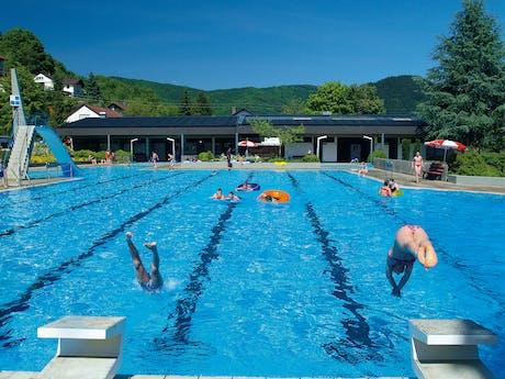 Verwarmd zwembad met duikplank en glijbaan