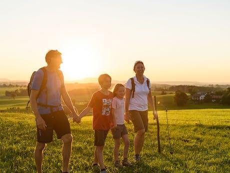 Familie wandelen in de zonsondergang